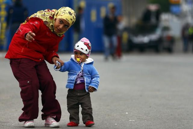 Deux enfants migrants marchent dans un camp de... (Photo Matthias Schrader, AP)