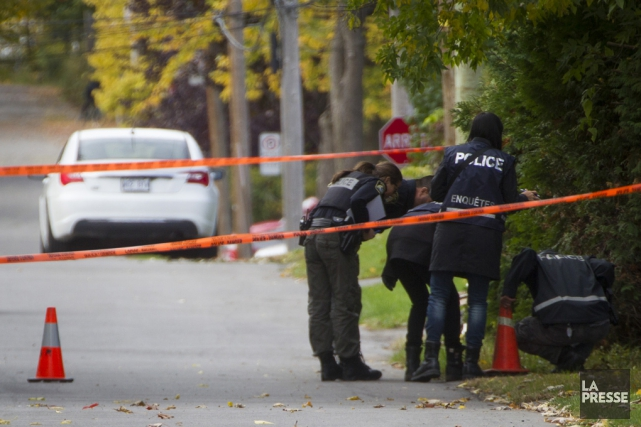 Des policiers examinent la scène de crime, au... (Ivanoh Demers, La Presse)