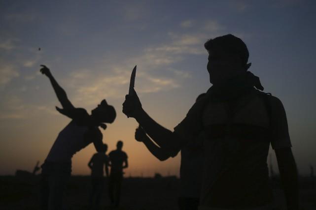 Palestiniens de Gaza brandissant des couteaux en direction... (AFP, Mohammed Abed)