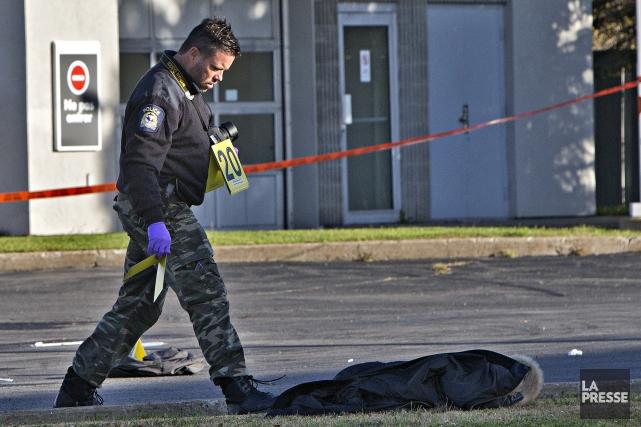 Des policiers examinent la scène du crime après... (PHOTO PATRICK SANFAÇON, LA PRESSE)