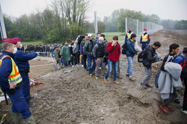 Dirigés par des policiers hongrois, des migrants continuent... (PHOTO HANNA SONIA, AFP)