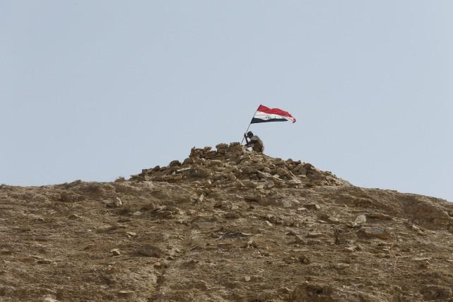 Un combattant chiite hisse un drapeau au sommet... (Photo Thaier Al-Sudani, Reuters)