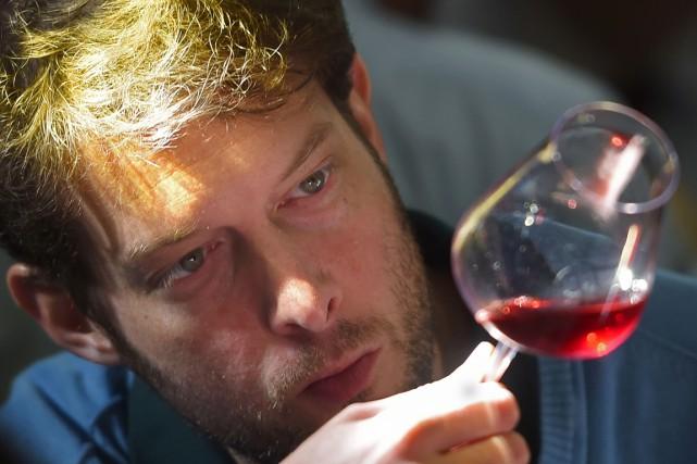 Un participant sud-africain analyse un vin lors duChampionnat... (PHOTO BORIS HORVAT, AFP)