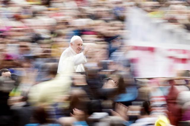 Le pape François salue la foule depuis la... (PHOTO ANDREW MEDICHINI, AP)