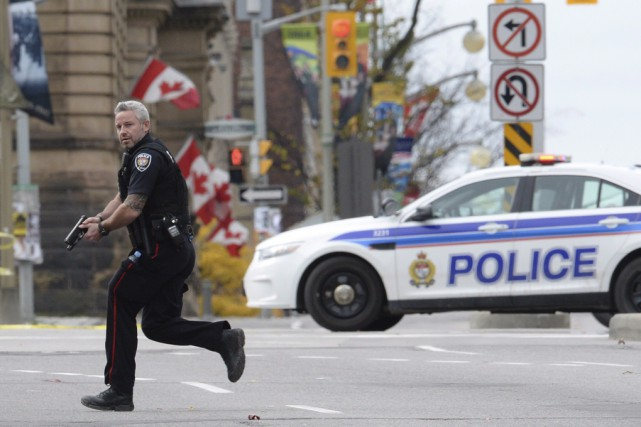 Un officier de police d'Ottawa court, son arme... (Archives La Presse Canadienne)