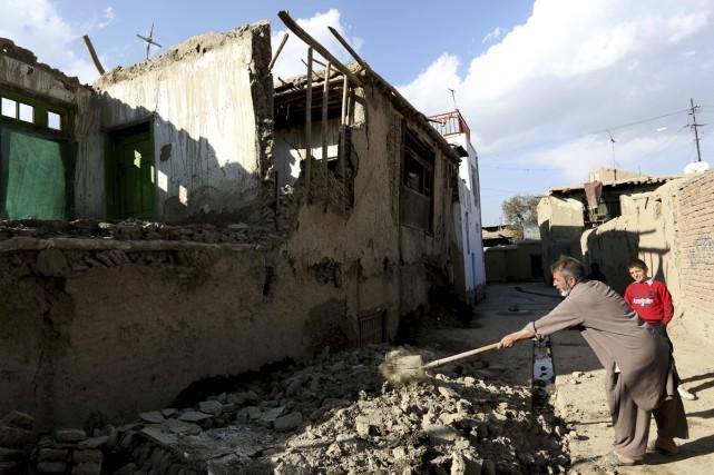 Un Afghan nettoie les décombres d'une maison après... (Rahmat Gul, Associated Press)