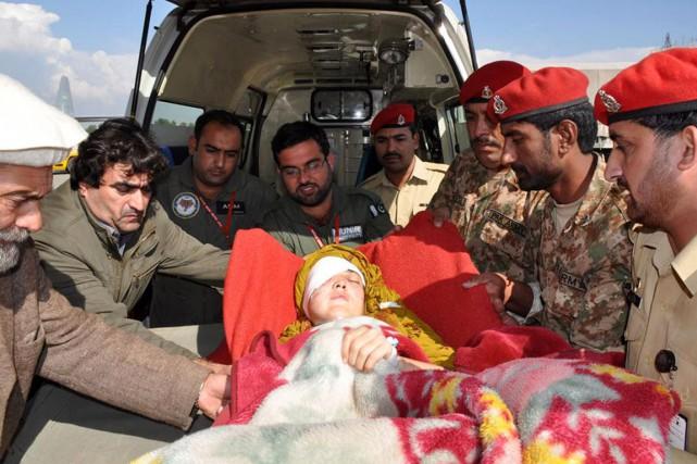 Des membres d'une équipe médicale de l'armée pakistanaise... (PHOTO AFP)