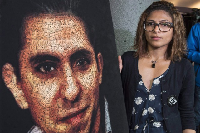 Ensaf Haidar aux côtés d'une illustration du visage... (Photo archives La Presse Canadienne)