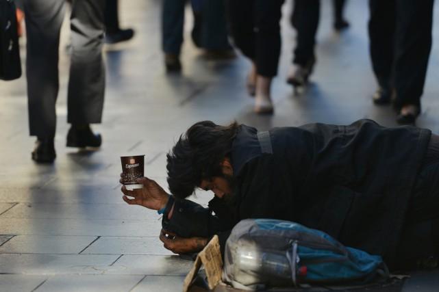 Un sans-abri mendie dans le quartier financier de... (Photo Peter PARKS, archives AFP)
