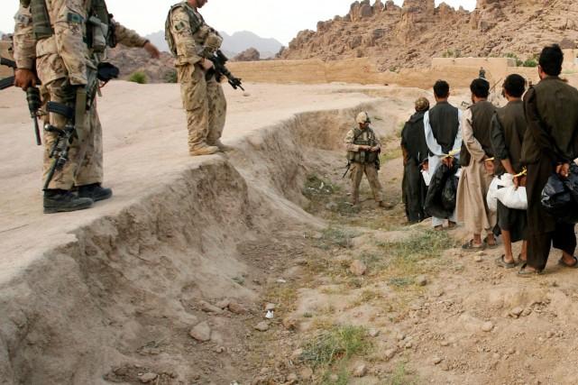 Des soldats canadiens gardent des prisonniers afghans soupçonnés... (PHOTO JOHN D. McHUGH, ARCHIVES AFP)