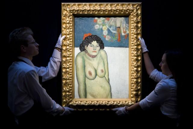 Des employés de Sotheby's exhibent La Gommeuse, de... (Photo JUSTIN TALLIS, AFp)