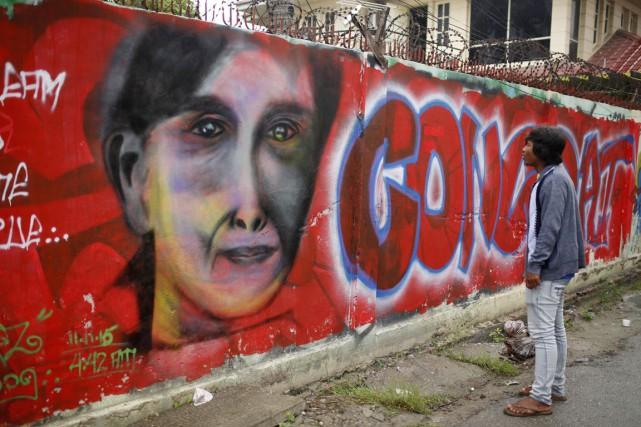 Un homme regarde un graffiti qui salue la... (PHOTO HKUN LAT, AP)
