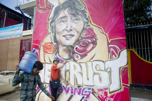 Une femme pose devant un graffiti illustrant Aung... (PHOTO YE AUNG THU, AFP)