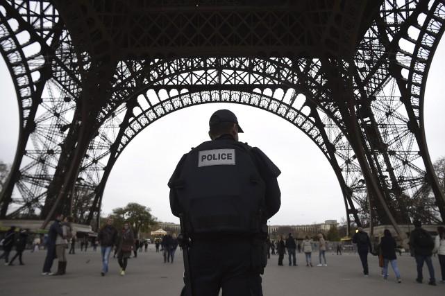 Un policier patrouille près de la tour Eiffel,... (Agence France-Presse)