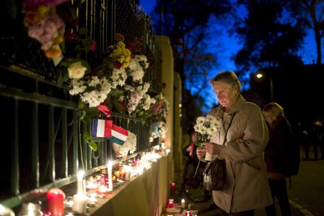 Une femme dépose des fleurs devant l'ambassade française,... (Associated Press)