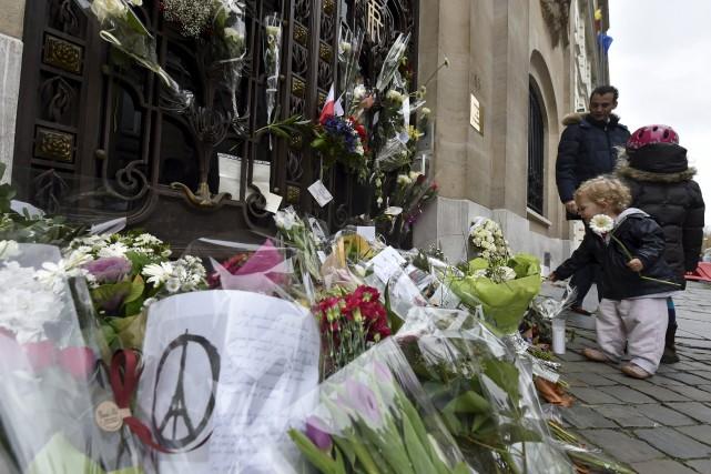 Un petit garçon dépose une fleur devant l'ambassade...
