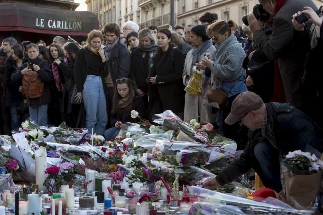Des personnes se recueillaient, dimanche, devant les sites... (Peter Dejong, Associated Press)