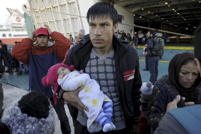 Des réfugiés et des migrants débarquent du navireEleftherios... (PHOTO MICHALIS KARAGIANNIS, REUTERS)