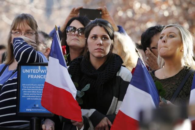 Brandissant des drapeaux français, une rose à la main, des centaines de... (PHOTO AP)
