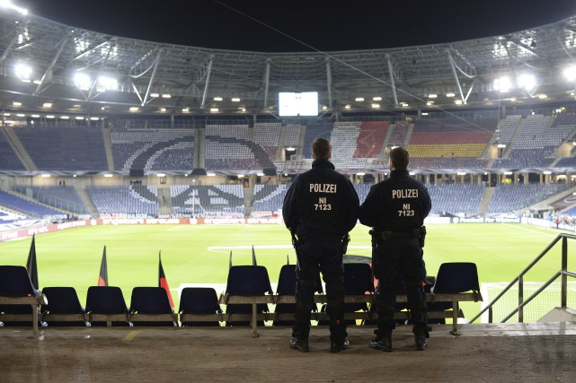 Deux policiers montent la garde dans le stade... (Julian Stratenschulte, Associated Press)
