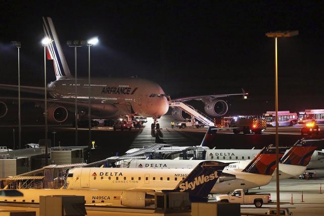 Des véhicules d'urgence sont stationnés près de l'avion... (AP, Ravell Call)