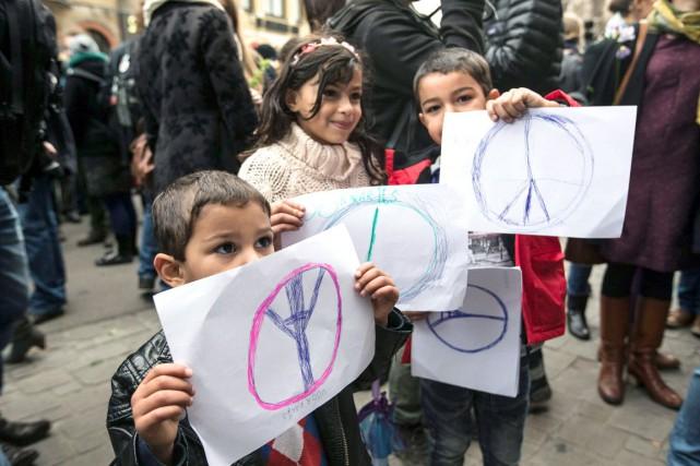 Des enfants tiennent des dessins de «#PaixpourParis» dans... (AFP, Kurt Desplenter)