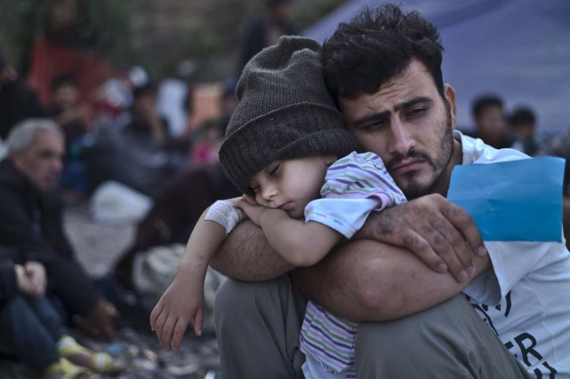 Un Syrien tombe de fatigue avec son fils,... (Associated Press)