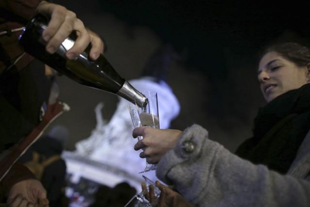 Des Parisiens boivent du champagne lors d'un rassemblement... (PHOTO KENZO TRIBOUILLARD, AFP)