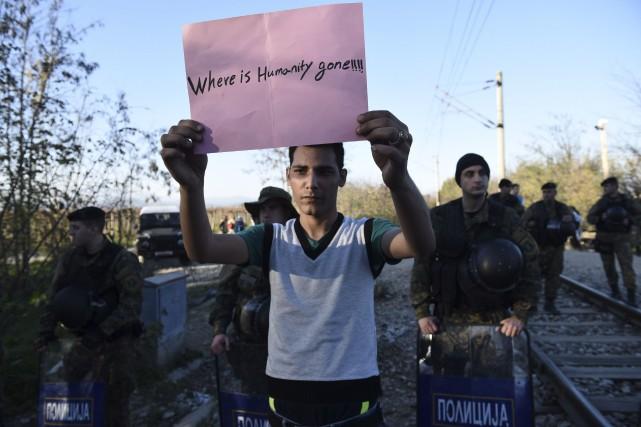 Un migrant tient une affiche disant «Où s'en... (AP, Giannis Papanikos)