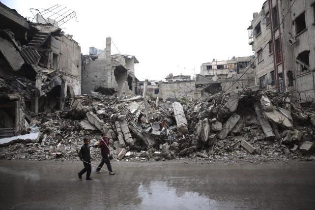 Des enfants syriens marchent à travers les ruines... (AFP, Abd Doumany)