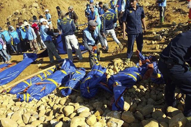 Les corps des mineurs sont extirpés tranquillement des... (Agence France-Presse)