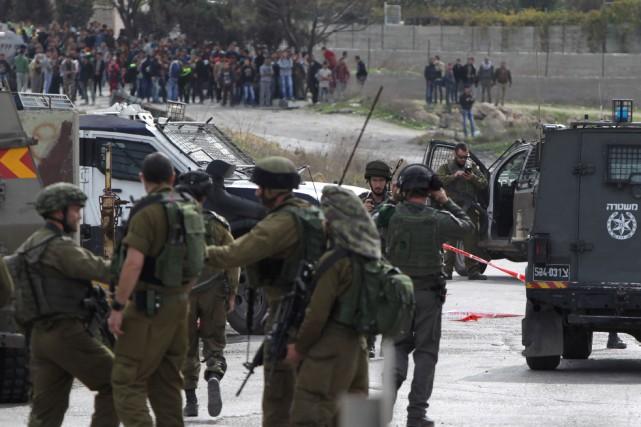 Des jeunes Palestiniens observent de loin alors que... (PHOTO HAZEM BADER, AGENCE FRANCE-PRESSE)