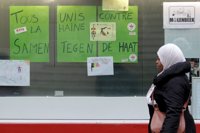 Une dame marche devant une affiche dans la... (PHOTO FRANÇOIS WALSCHAERTS, ASSOCIATED PRESS)
