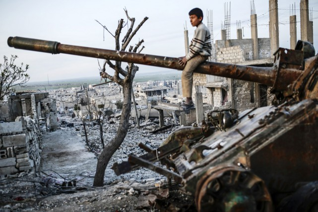 Un garçon kurde est assis sur le canon... (PHOTO YASIN AKGUL, ARCHIVES AFP)