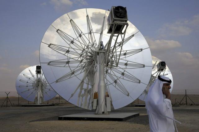 Un homme passe devant des panneaux solaires à... (PHOTO REUTERS)