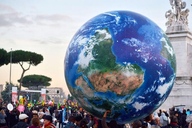 Des gens portent un ballon géant représentant la... (AFP, Tiziana Fabi)