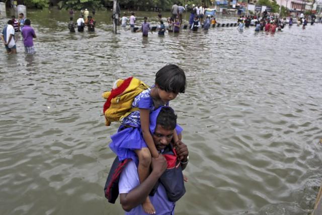 Un homme porte sur ses épaules une jeune... (PHOTO REUTERS/STRINGER)