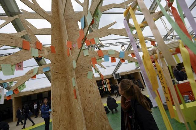 Une visiteuse passe devant un «arbre aux solutions»,... (AFP, Miguel Medina)
