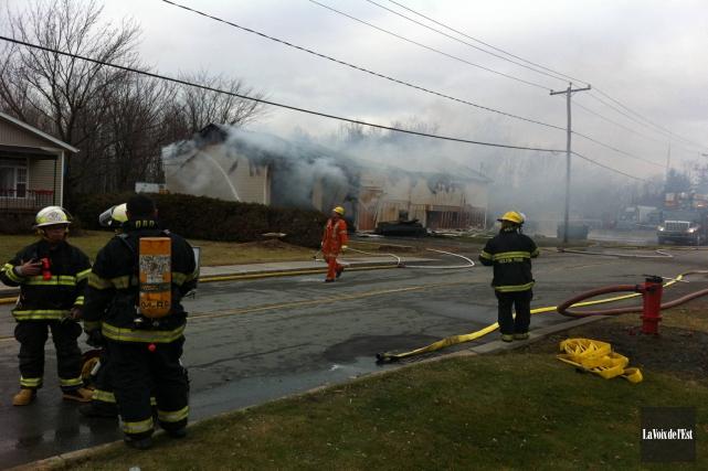 Les pompiers combattent un incendie dans un garage... (Photo Cynthia Laflamme, La Voix de l'Est)
