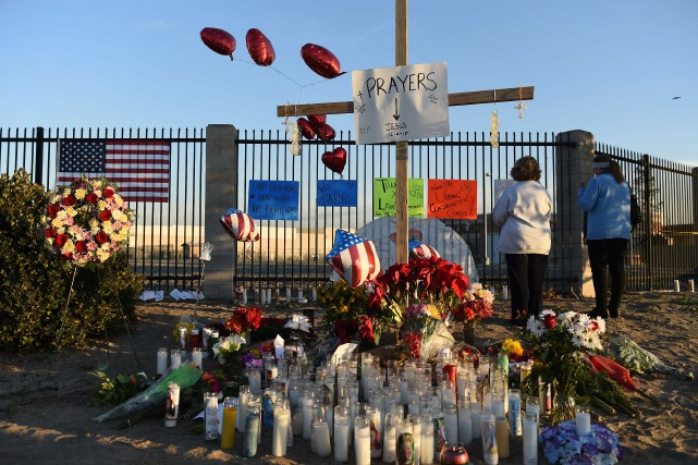 Des gens prient près d'un mémorial en hommage... (PHOTO ROBYN BECK, AGENCE FRANCE-PRESSE)