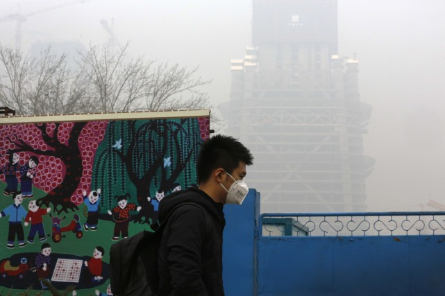 Une journée sous le smog à Pékin.... (Associated Press)