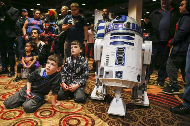 Des enfants assis à côté de R2-D2 assistent... (PHOTO REUTERS)