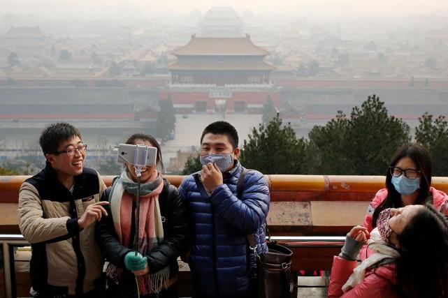 La pollution atmosphériquene semble pas importuner ces touristes.... (AP, Andy Wong)