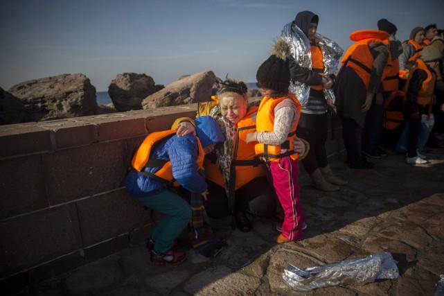 Une mère pleure alors qu'elle serre ses enfants... (PHOTO SANTI PALACIOS, AP)