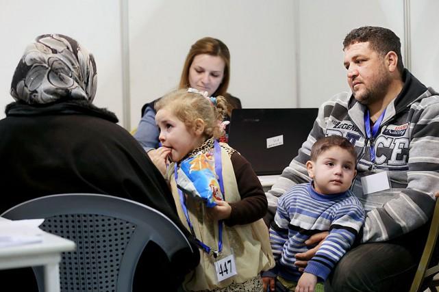 Des réfugiés syriens attendent à l'aéroport à Amman... (AP, Raad Adayleh)