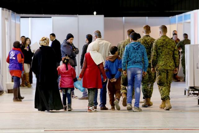 Des réfugiés à leur arrivée à l'aéroport.... (Associated Press)