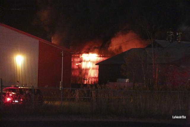 Un violent incendie faisait toujours rage vers 22h15... (Catherine Trudeau, La Voix de l'Est)