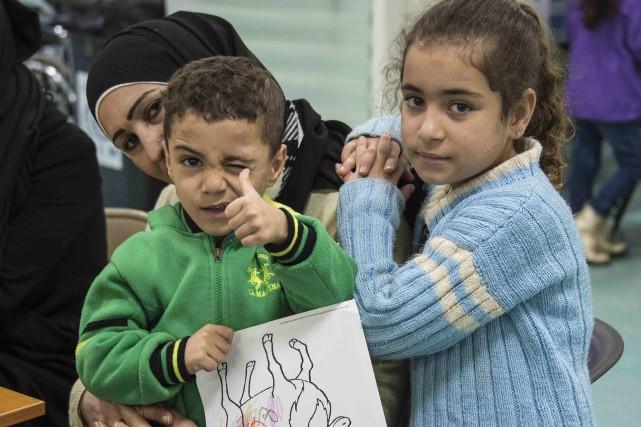 Deux enfants syriens posent avant l'embarquement des réfugiés... (PHOTO REUTERS)