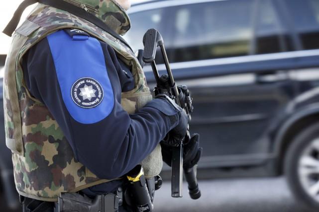 Un garde-frontière suisse lourdement armé inspecte un véhicule... (Salvatore Di Nolfi, Keystone/AP)