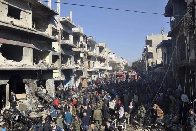 Des résidants du quartier constatent les dégâts causés... (PHOTO AGENCE FRANCE-PRESSE)